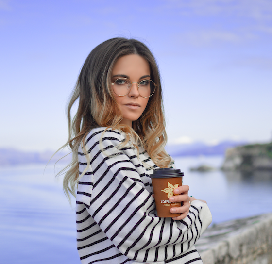A woman wearing a striped blouse, holding a coffee cup in front of a river.